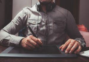 A importância da transcrição é imensa. Na imagem um homem de headphones e tablet trabalha.